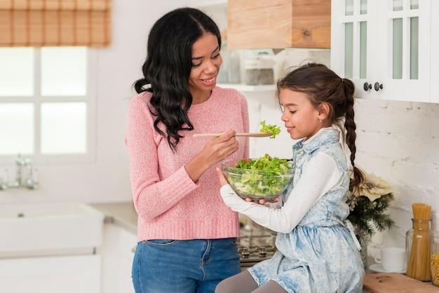 Joven madre alimentando a su hija