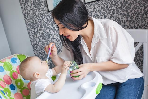 Joven madre alimentando a su pequeño bebé