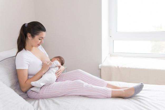 Joven madre amamantando, amamantando y abrazando al bebé