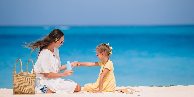 Joven madre aplicando crema solar a la nariz de la hija en la playa. proteccion solar