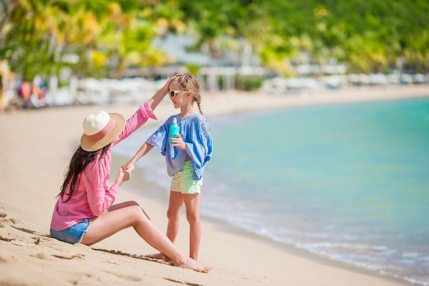 Joven madre aplicando protector solar en su hijo