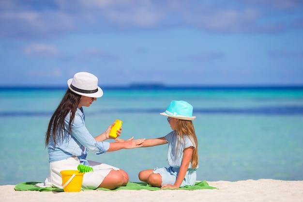 Joven madre aplicar protector solar a su hijo