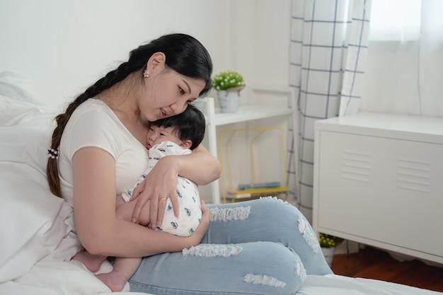 Joven madre asiática hermosa con su pequeño bebé recién nacido lindo