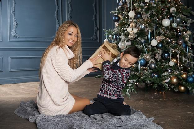 Joven madre asiática hermosa con su pequeño hijo sentado cerca de un árbol de navidad decorado e intercambiar regalos.