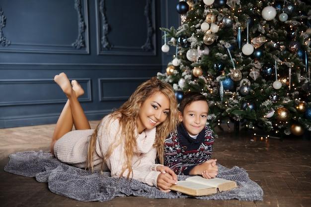 Joven madre asiática hermosa con su pequeño hijo sentado cerca de un árbol de navidad decorado y leyendo un libro.