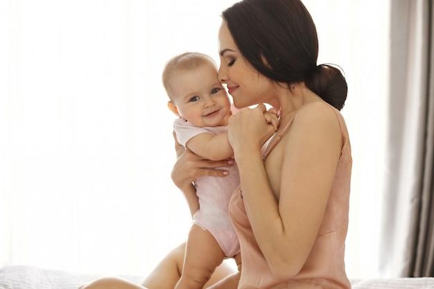 Joven madre atractiva en ropa de dormir sonriendo abrazando besando a su bebé sentado en la cama sobre la ventana ojos cerrados.