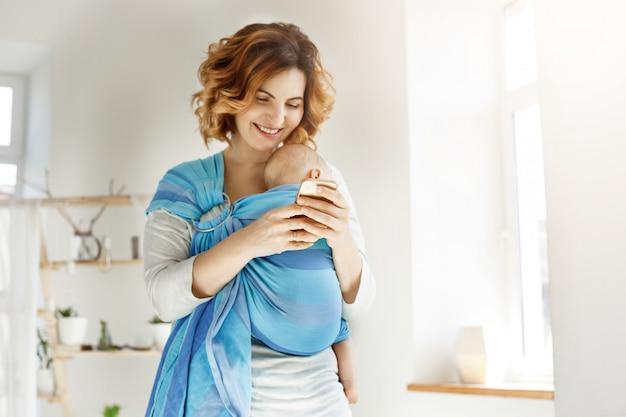 Joven madre atractiva sonríe y mira a través de fotos de su hijo en el teléfono celular