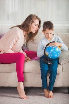 Joven madre ayudando a su hijo a hacer la tarea. familia eligiendo dónde viajar en vacaciones. madre y su hijo sosteniendo un globo