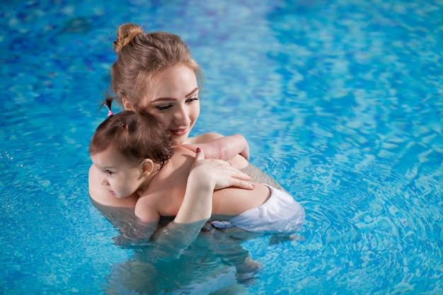 Joven madre baña al bebé en la piscina.