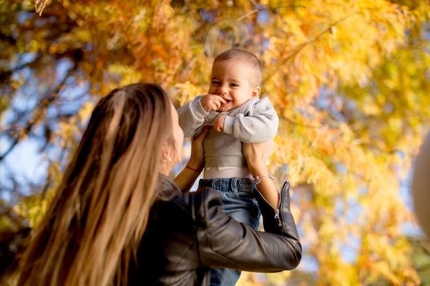 Joven madre y bebé en el parque de otoño