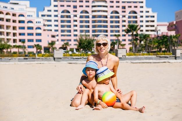 Joven madre en bikini juega en la playa con hijos