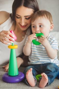 Joven madre bonita jugando con su pequeño hijo. familia alegre divirtiéndose en el interior con pequeño hijo