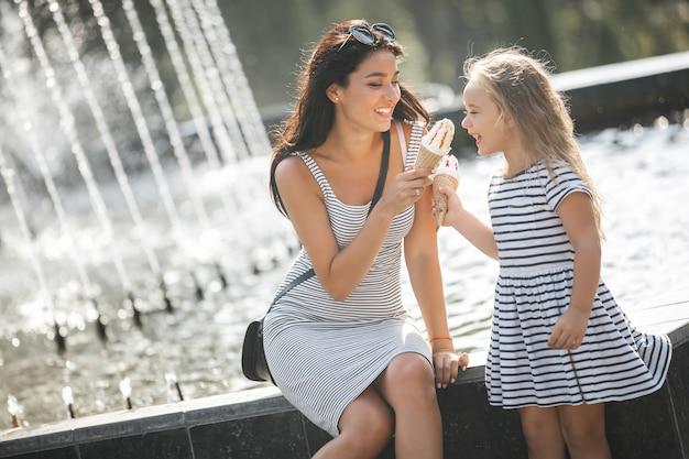 Joven madre bonita y su hija divirtiéndose juntos cerca de la fuente. hermosa mujer y su pequeño niño comiendo helado. familia alegre divirtiéndose.