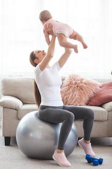 Joven madre bonita trabajando con su pequeño hijo en casa