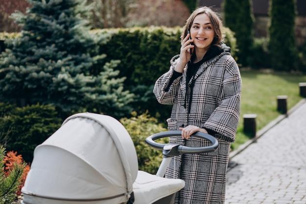 Joven madre caminando con carro de bebé en el parque y hablando por teléfono