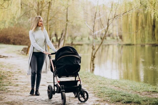Joven madre caminando con carro de bebé en el parque