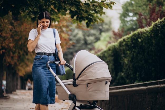 Joven madre caminando con cochecito en el parque y hablando por teléfono