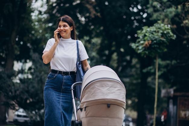 Joven madre caminando en el parque con cochecito de bebé y hablando por teléfono