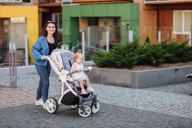 Joven madre caminando con su bebé y lo lleva en un hermoso cochecito. felicidad.
