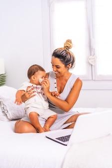 Joven madre caucásica con su hijo en la habitación de la cama teletrabajando y cuidando a su hijo