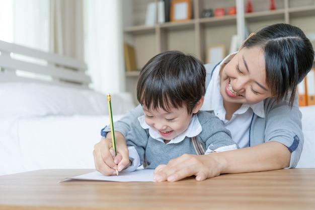 Joven madre cogió la mano del hijo sosteniendo un lápiz para el sarampión escribir en papel blanco, preescolar en casa