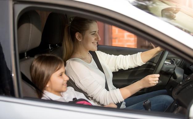 Joven madre conduciendo coche a la escuela con hija