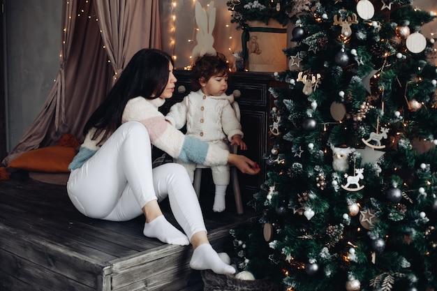 La joven madre se divierte mucho con su bebé cerca del árbol de navidad en casa