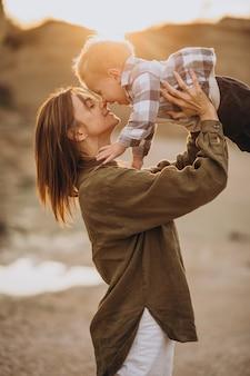 Joven madre divirtiéndose con su pequeño hijo