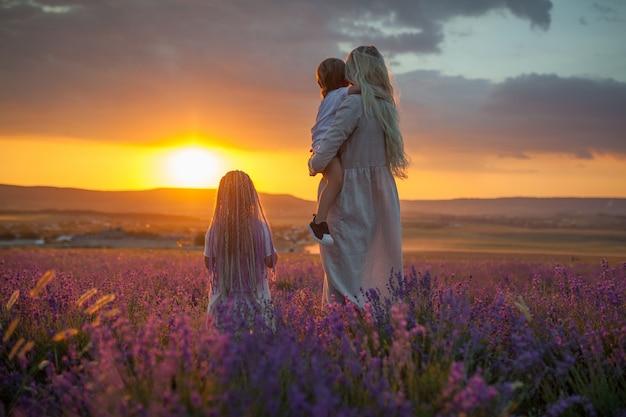 Una joven madre con dos hijos mirando el sol saliente en un campo de lavanda