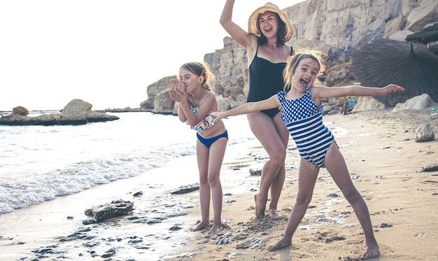 Una joven madre y dos pequeñas hijas se divierten, bailan y ríen en la orilla del mar. familia feliz de vacaciones.