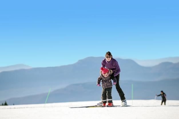 Joven madre e hija en vacaciones de esquí