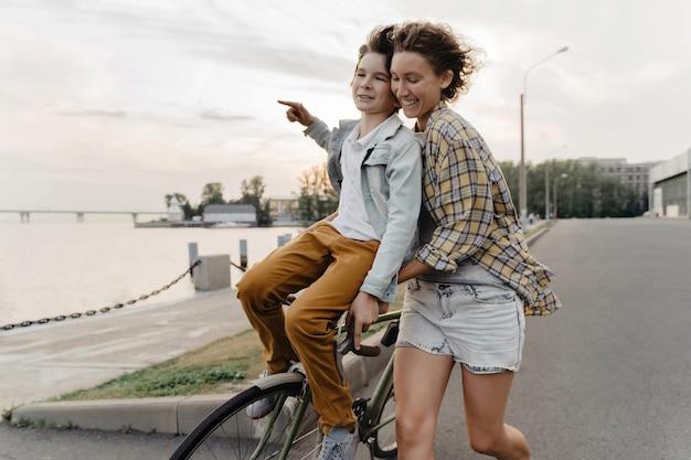 Joven madre e hijo divirtiéndose mientras monta en bicicleta