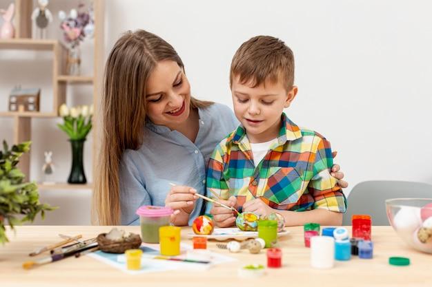 Joven madre e hijo pintando huevos para pascua