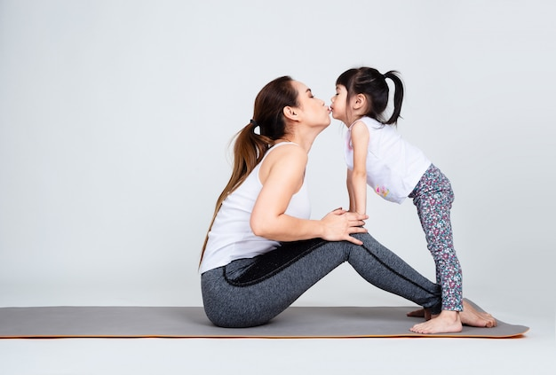 Joven madre entrenando encantadora hija con gimnasia