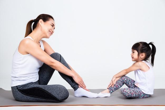 Joven madre entrenando encantadora hija con yoga