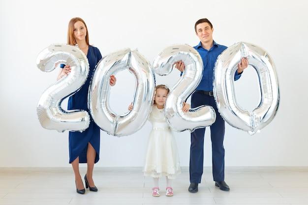 Joven madre de familia feliz y padre e hija sosteniendo globos con forma de números 2020. año nuevo