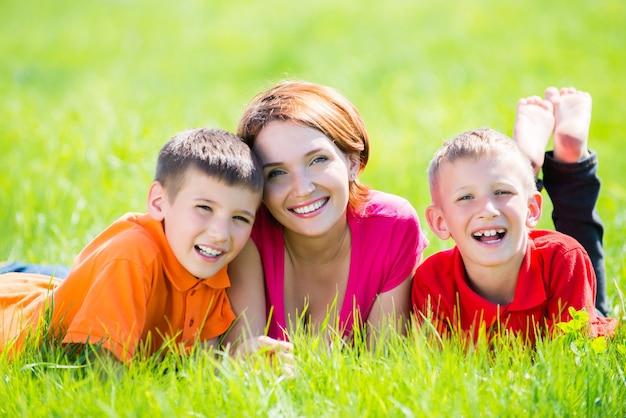 Joven madre feliz con niños en el parque