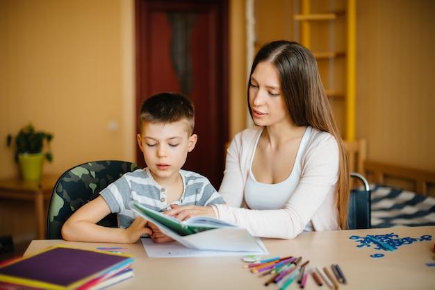 Una joven madre está haciendo la tarea con su hijo en casa. padres y entrenamiento