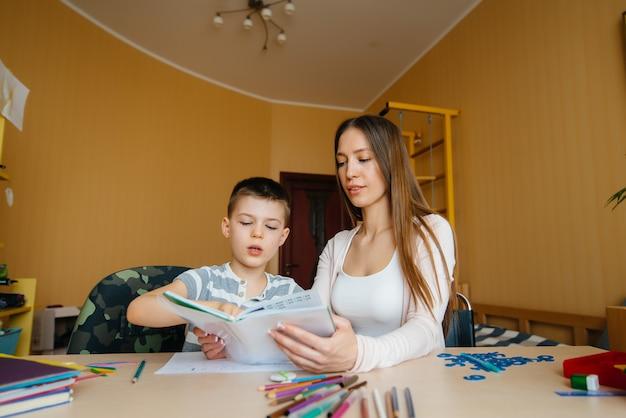 Una joven madre está haciendo la tarea con su hijo en casa. padres y formación.