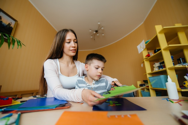 Una joven madre está haciendo la tarea con su hijo en casa
