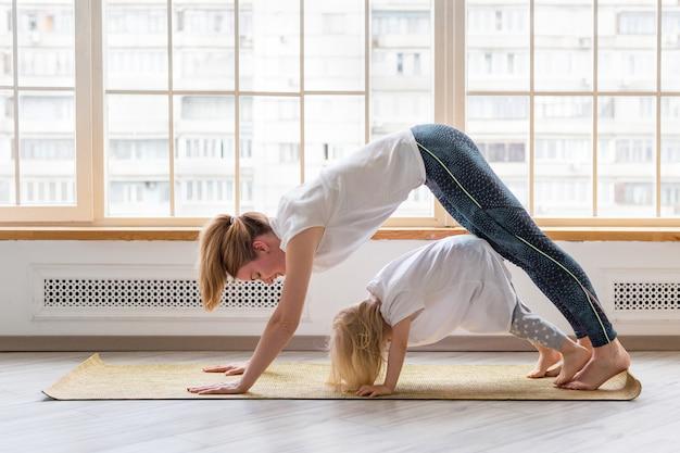 Joven madre haciendo yoga con una niña de 3 años delante de la ventana. pose de asana de perro mirando hacia abajo
