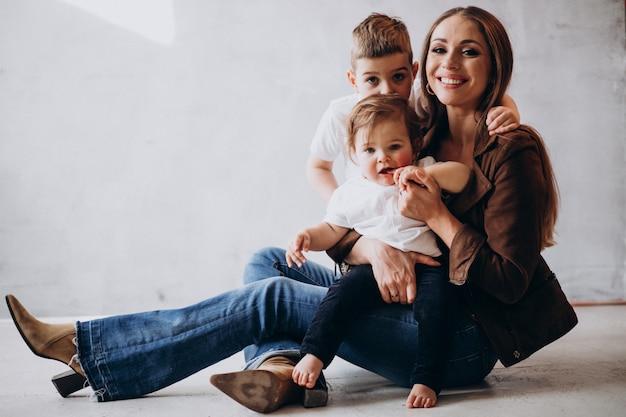 Joven madre hermosa con dos hijos