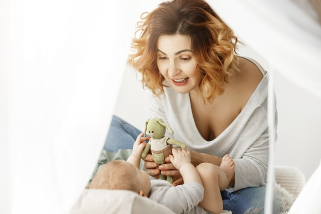 Joven madre hermosa feliz jugando con su preciosa mujer bebé en la acogedora cama grande. mujer que le da a su bebé lindo juguete conejo verde. concepto de familia