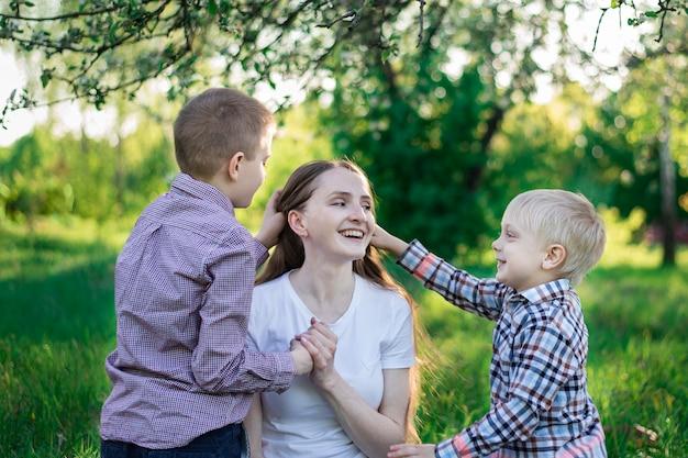 Joven madre hermosa jugando con sus dos hijos. niños acariciando la cabeza de mamá.