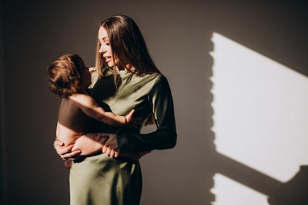 Joven madre hermosa con su hijo pequeño, practicando la lactancia materna