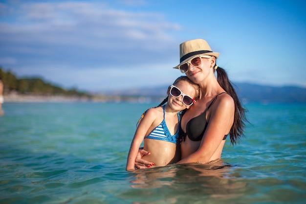 Joven madre hermosa y su pequeña hija adorable en la playa