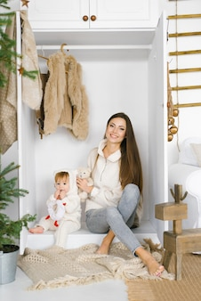 Joven madre con una hija de un año está sentada en un armario