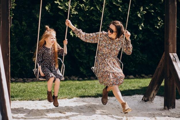 Joven madre con hija balanceándose en el patio trasero