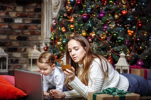 Joven madre con una hija compra regalos usando laptop y tarjeta de crédito