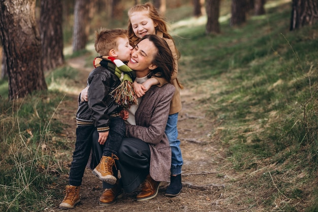 Joven madre con hija e hijo en el bosque